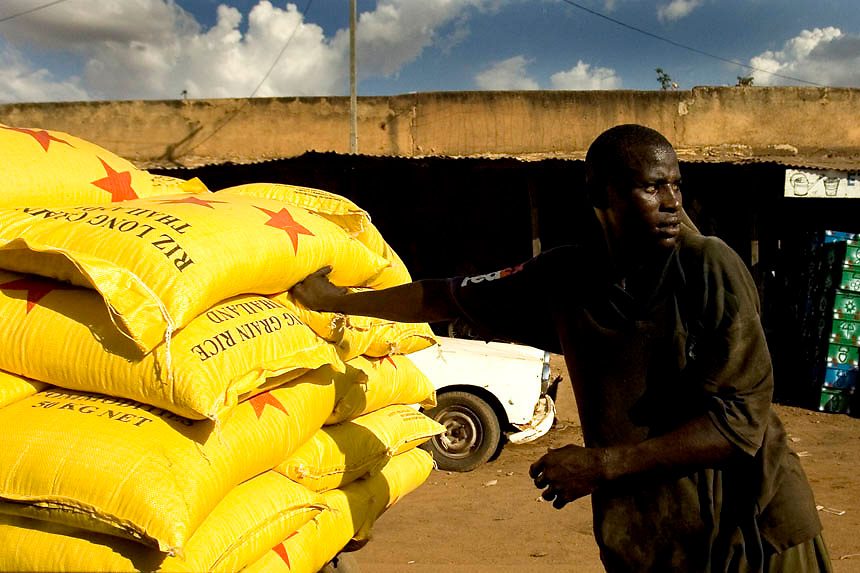 A man carries sacks of rice in a market downtown Ouagadougou, Burkina Faso. Rice has become preferred by people living in urban areas as it was cheap and easy to cook. Burkina imports two-third of the rice but farmers are to invest in rice farming following Fao's  intention to breathe life into national agricolture by producing and profiting from rice.