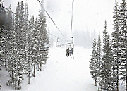 SHOT 2/12/12 4:08:00 PM - Skiers ride a chair lift as heavy snow falls at Monarch Ski and Snowboard Area. Monarch is located on U.S. Highway 50. It is twenty miles west of Salida, Colorado, on Monarch Pass and has 54 trails, two terrain parks, and a newly-opened Extreme-Terrain area called Mirkwood. Monarch fist opened in 1939 with one rope tow running up the infamous Gunbarrel run, a long, steep, heavily moguled run..(Photo by Marc Piscotty / © 2012)