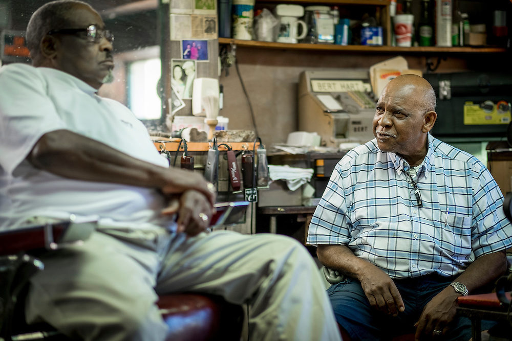 80-year-old Bert Hart (right) has been cutting hair in his Aliquippa barber shop for the past 60 years. Hart moved to Aliquippa in the boom times of the 1960&rsquo;s and opened Bert&rsquo;s Barber Shop in 1966.<br /> <br /> At that time the town was home to over 26,000 people but most of the homes and businesses along his street are gone as well as most of the people.<br /> <br /> At one time Hart owned three adjacent buildings, housing a bar, apartment building and the barber shop, in the Plan 11 neighborhood.<br /> <br /> The three-chair shop is a place where people hang out here and talk about everything from politics to religion and sports as well as the good old days when Aliquippa was thriving.