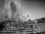 Incense smoke from copal resin washes over indigenous Mayan people resting on the steps of Iglesia (church) de San Tomas, where Mayan rituals mingle with Catholicism on a plaza dating back to 1540.  Chichicastenango, Guatemala.