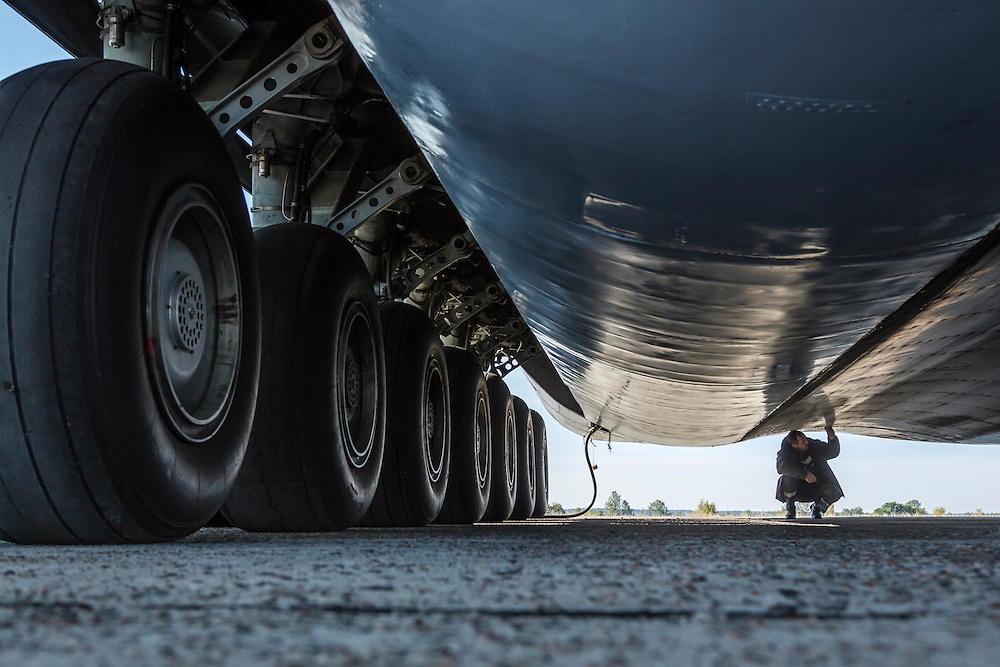 GOSTOMEL, UKRAINE - OCTOBER 1, 2014: A maintenance worker inspects underneath the Antonov AN-225, the longest and heaviest airplane ever built, on an airfield in Gostomel, outside Kiev, Ukraine. CREDIT: Brendan Hoffman for The New York Times