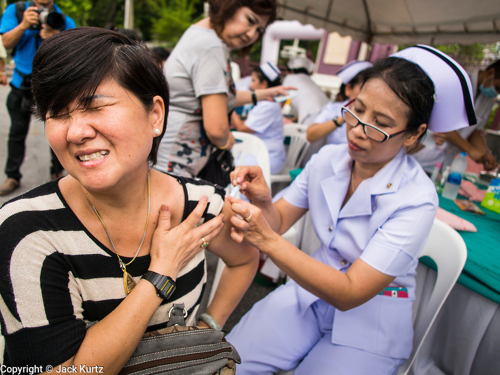 """15 JUNE 2014 - BANGKOK, THAILAND: A woman gets an immunization during a health and wellness screening at a """"Return Happiness to Thais"""" party in Lumpini Park in Bangkok. The Thai military junta, formally called the National Council for Peace and Order (NCPO), is sponsoring a series of events throughout Thailand to restore """"Happiness to Thais."""" The events feature live music, dancing girls, military and police choirs, health screenings and free food.   PHOTO BY JACK KURTZ"""