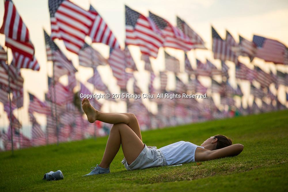 9月10日,在美国加利福尼亚州洛杉矶的马里布,一名少女在旗帜中间休息。当天,在美国&ldquo;9&middot;11&rdquo;事件十四周年前夕,佩珀代因大学的学生和教职员工在学校草坪上插起约3000面美国国旗,纪念&ldquo;9&middot;11&rdquo;事件遇难者。新华社发(赵汉荣摄)<br /> A takes rest amongst 3,000 US flags are displayed at Pepperdine University to mark the 14th anniversary of the 9/11 terror attack, September 10, 2015 in Los Angeles, California, the United States. (Xinhua/Zhao Hanrong)Photo by Ringo Chiu/PHOTOFORMULA.com)
