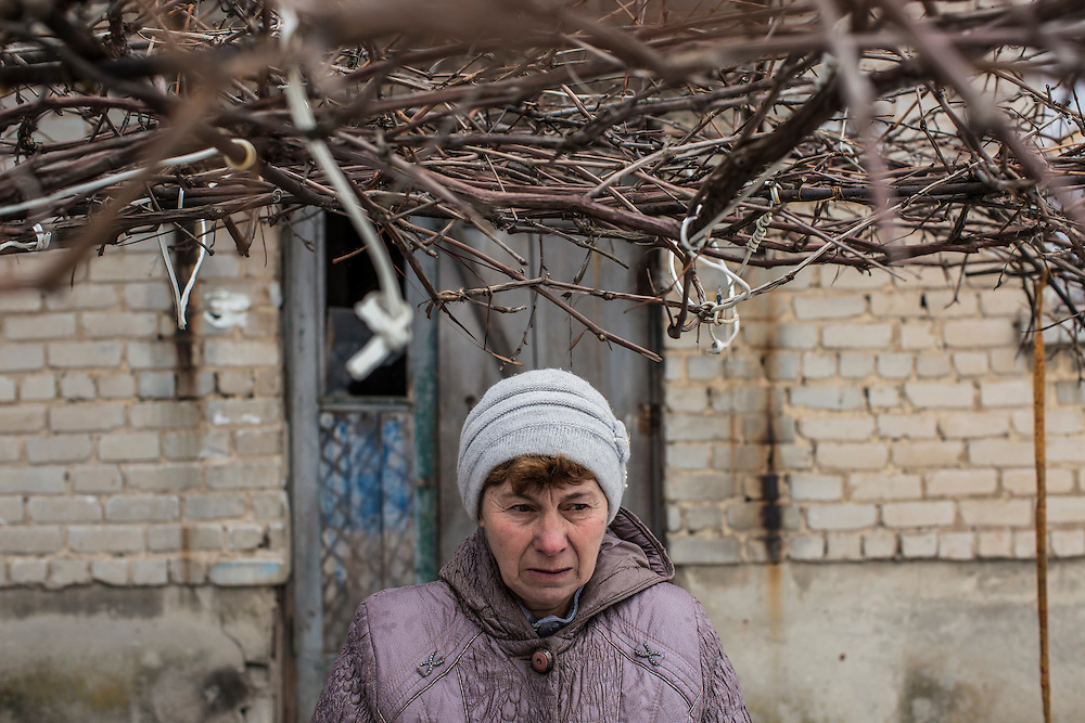 GRABSKOYE, UKRAINE - JANUARY 24, 2015: Lyudmila Styopina outside her apartment building, which was hit by rockets over the summer and heavily damaged in Grabskoye, Ukraine. Only a handful of residents are left in the town after heavy fighting drove most away. CREDIT: Brendan Hoffman for The New York Times