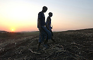 "Sugarcane cutters walk through a field of freshly cut sugarcane after a ""burn"" of underbrush in a nearby field on Sunday evening, September 10, 2006 in Empangeni, South Africa."