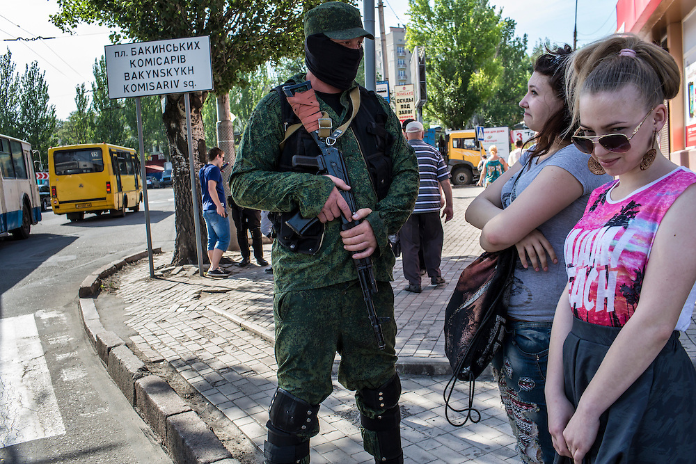 DONETSK, UKRAINE - MAY 20: A member of the Vostok Battalion, a pro-Russia militia, talks to women while guarding an intersection on May 20, 2014 in Donetsk, Ukraine. A week before presidential elections are scheduled, questions remain whether the eastern regions of Donetsk and Luhansk are stable enough to administer the vote. (Photo by Brendan Hoffman/Getty Images) *** Local Caption ***