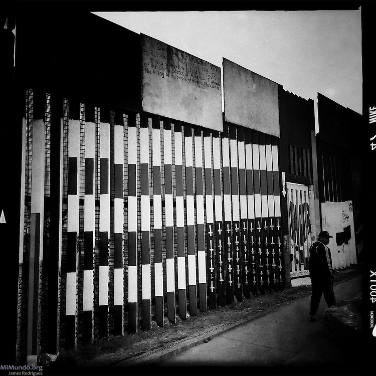 A man walks by an upside down US flag with crosses instead of stars painted along the Mexico-US border. Tijuana, Baja California, Mexico. May 30, 2015.