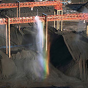 Aerial view of coal depot at Newport News, Virginia on the James River. A rainbow is seen in the water sprayed on the coal to keep the dust under control. This stockpile of coal is mined in Western Virginia and West Virginia, transported by rail to Hampton Roads (Newport News, Hampton, Norfolk region) for export on cargo ships.