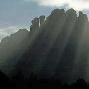 Vibrant God beams, called crepuscular rays, form over Cathedral Rock, a towering mountain near Sedona, Arizona. The beams form when the sun shines into fog or mist. The columns at the summit of Cathedral Rock cast three-dimensional shadows between the rays.