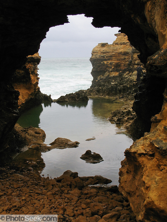 """At Twelve Apostles Marine National Park, the Indian Ocean (or Southern Ocean according to Australian geographers) carves """"The Grotto"""" sea arch from soft miocene limestone bluffs of Port Campbell National Park, along the Great Ocean Road, Victoria, Australia. The Great Ocean Road (B100) is a 243-km highway along the southeast coast of Australia between Torquay and Warrnambool, in the state of Victoria. Dedicated to casualties of World War I, the Great Ocean Road was built by returned soldiers between 1919 and 1932 and is the world's largest war memorial."""