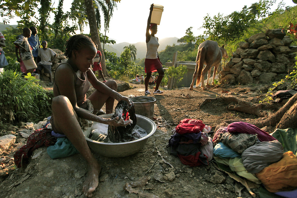 A young woman washes her clothes at the site of a natural spring high on the mountainside above Carrefour, Haiti.  All the mountain people make their way to the spring to wash their clothes and collect drinking water for their families.