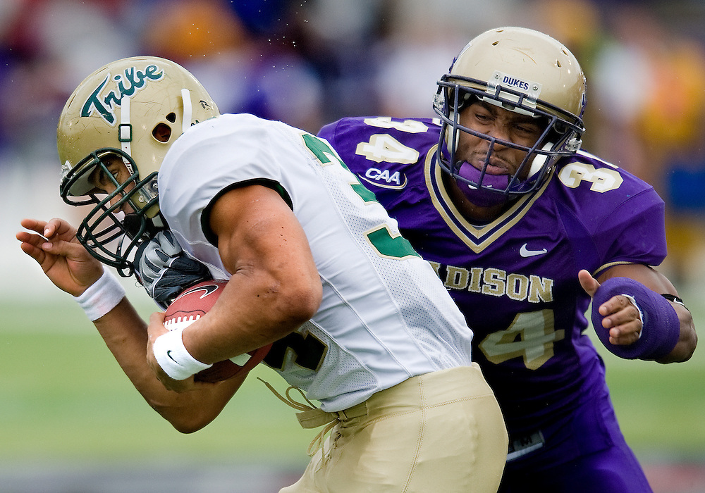 James Madison's Marcus Haywood gets an arm around William and Mary running back Jonathan Grimes during first quarter action at Bridgeforth Stadium in Harrisonburg Saturday. JMU beat the Tribe 48-24.