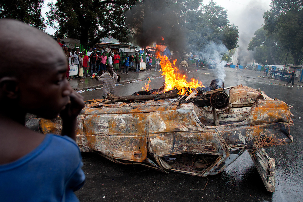 A car burns as a roadblock. Protestors are taking to the streets for the second day in a row in response to Haiti's election results which were announced on Tuesday December 7th among allegations of fraud.