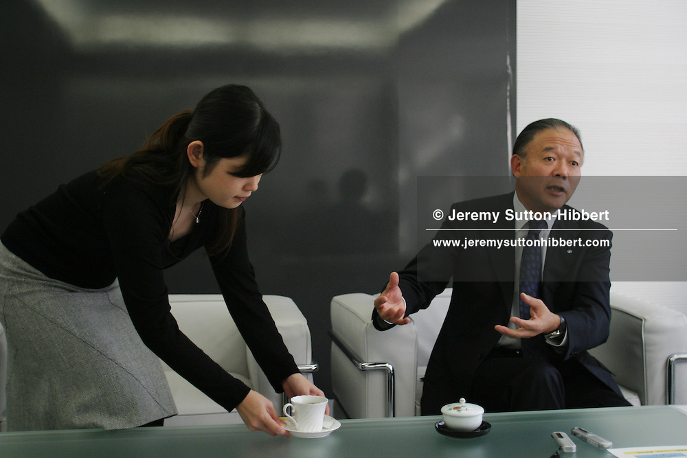 """An employee brings  coffee for Tadahiro Yoshida, President and CEO, of YKK Corporation ('YKK' has a 50% share of the worlds market in zip and """"fasteners"""" manufacturing) during an meeting, in Tokyo, Japan on Monday, Nov. 29th 2004. During interviews it is common for female assistants to enter the rooms silently , bringing refreshment drinks of green tea, coffee, or orange juice, to the company head and his guests."""