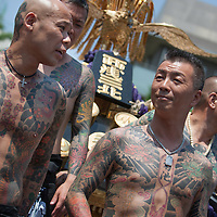 Members of the Takahashi-gumi Japanese yakuza crime syndicate wait with their mikoshi portable shrine before carrying it through the streets as part of the 2nd day of the Sanja festival, at Asakusa Shrine in Asakusa district, in Tokyo, Japan, Saturday May 19th 2012.