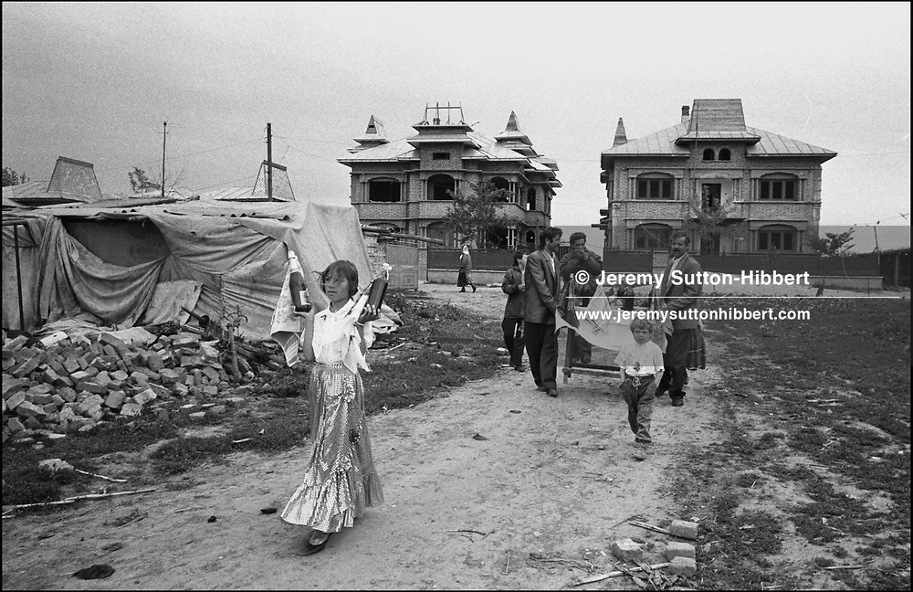 ROMANIAN ORTHODOX EASTER CELEBRATIONS, THE MOST IMPORTANT HOLIDAY OF THE YEAR FOR THE GYPSIES. ZAMBILA MIHAI CARRIES   WINE TO THE HOUSE OF HER BROTHER PUIA'S GODFATHER. PUIA IS IN FRONT OF THE TABLE, HANDS IN POCKET. SINTESTI, ROMANIA, EASTER 1994..©JEREMY SUTTON-HIBBERT 2000..TEL./FAX. +44-141-649-2912..TEL. +44-7831-138817.