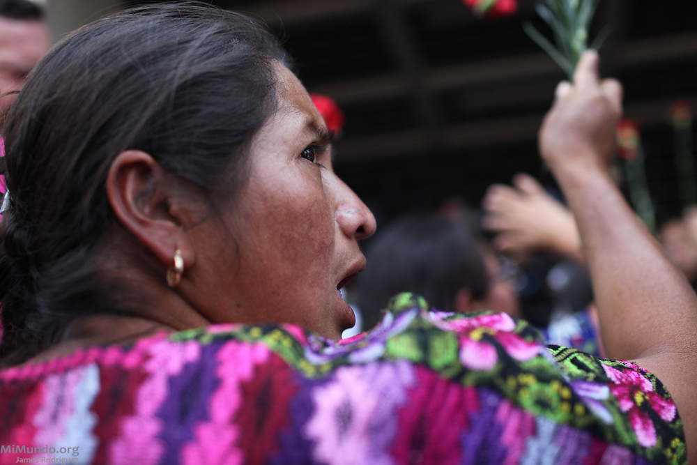 People hold red carnations, symbols of wartime victims, as they protest in front of the Constitutional Court. Despite the trial's suspension ordered by High Risk Court Judge Carol Flores on the previous day, Judge Jazmin Barrios reconvened the trial on the 21st day to decide on a course of action. Judge Barrios ruled that Judge Flores' annulment is illegal and will be asking the Constitutional Court, Guatemala's highest judicial body, to rule on the fate of the genocide trial. Guatemala, Guatemala. April 19, 2013.