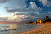 Large clouds and blue skies over the Indiana Restaurant Cottesloe with the pylon under repair and the golden hour just before sunset lighting up the beach sand.