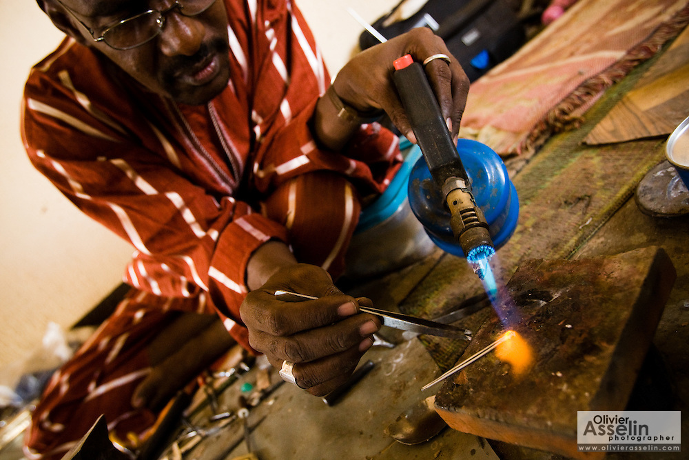 Man making silver jewelry at the Village Artisanal de Ouagadougou, a cooperative that employs dozens of artisans who work in different mediums, in Ouagadougou, Burkina Faso, on Monday November 3, 2008.
