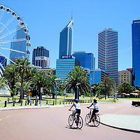 Cycling Past the Wheel of Perth at Barrack Square in Perth, Australia<br /> The exciting, modern city of Perth is in western Australia.  Its tall, glass skyscrapers are a backdrop to vineyards, Swan River cruises, welcoming parks and Indian Ocean beaches.  A giant Ferris wheel called the Wheel of Perth was a prominent feature of Barrack Square and Perth&rsquo;s skyline.  It closed in 2010.  A smaller version was built in Fremantle a year later.
