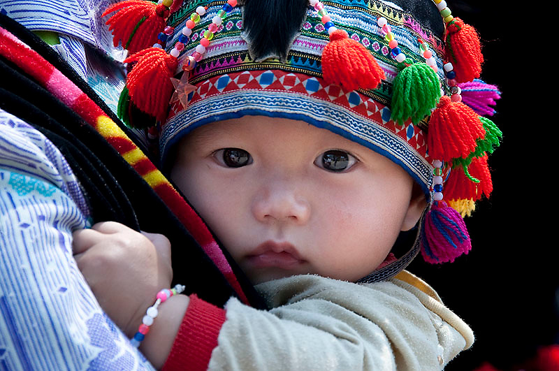 This Hmong baby is carried on his mothers back and wears a very bright and colourful hat handmade by the mother.
