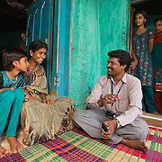 CAPTION: Gathering community data. Mobility India and CBM have partnered with Aptivate to develop a simple means of collecting key project-relevant data using relatively unsophisticated mobile phones. LOCATION: Sappayyanapura (village), Kasaba (hobli), Chamrajnagar (district), Karnataka (state), India. INDIVIDUAL(S) PHOTOGRAPHED: From left to right: Rakshitha S. V., Bhagya, P. Murthy, Shilpa C.B., Kavya S.N. and Manjula; background: Mahadevamma.