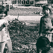 Three Roma kids playing with fresly cut grass around the Sarajevo railway station.