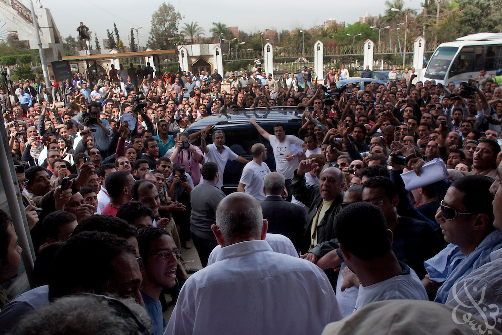 Egyptian Nobel Peace laureate and former UN atomic watchdog chief, Mohamed ElBaradei (c, white shirt, back to camera) heads through a crowd towards his vehicle following a visit to the  Egyptian Nile delta town of El Mansoura April 2, 2010. ElBaradei is thought to be a possible candidate to run against Egyptian President Hosni Mubarak in the 2011 presidential election, although he has not made a formal declaration as of yet.