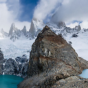 """On the border between Argentina and Chile, Mount Fitz Roy rises into clouds 2500 meters (8200 feet) above Lago Sucia (left) in Los Glaciares National Park, in the southern Andes mountains, Patagonia, Argentina, South America. Hike to the glacial cirque of Laguna de los Tres (right) from El Chaltén village, which was built in 1985 by Argentina to help secure the disputed border with Chile. The frontier tourist town of El Chaltén is 220 km (3 hours drive) north of the larger town of El Calafate. In 1877, explorer Perito Moreno named """"Cerro Fitz Roy"""" for Robert FitzRoy (no space before the capital R) who, as captain of the HMS Beagle, had travelled up the Santa Cruz River in 1834 and charted much of the Patagonian coast. First climbed in 1952 by French alpinists Lionel Terray and Guido Magnone, Mount Fitz Roy (3405 meters or 11,170 feet elevation) has fickle, windy weather and is one of the world's most challenging technical ascents. It is also called Cerro Chaltén, Cerro Fitz Roy, and Monte Fitz Roy (with a space before the R). Chaltén comes from a Tehuelche (Aonikenk) word meaning """"smoking mountain"""" (explained by frequent orographic clouds). Cerro is a Spanish word meaning hill. The foot of South America is known as Patagonia, a name derived from coastal giants, Patagão or Patagoni, who were reported by Magellan's 1520s voyage circumnavigating the world and were actually Tehuelche native people who averaged 25 cm (or 10 inches) taller than the Spaniards. Mount Fitz Roy is the basis for the Patagonia company's clothing logo, after Yvon Chouinard's ascent and subsequent film in 1968. Panorama stitched from 5 overlapping photos."""