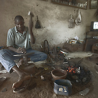 A jewellery artisan hammers a silver strip on an anvil at his studio, Ségou, Mali.