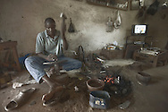 A jewellery artisan hammers a silver strip on an anvil at his studio, Ségou, Mali.