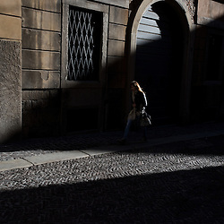 Bergamo, Italy - A woman walks in the historical centre of Upper Bergamo (Bergamo Alta) at sunset