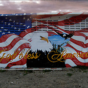 God Bless America and the American Flag with American Eagle painted on side of building.<br />
