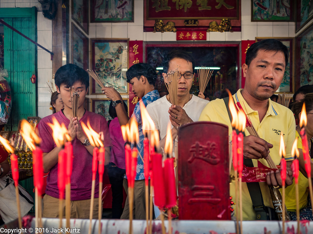 "07 FEBRUARY 2016 - BANGKOK, THAILAND: People light incense to make merit for Chinese New Year at a small Chinese shrine in Bangkok's Chinatown. Chinese New Year, also called Lunar New Year or Tet (in Vietnamese communities) starts Monday February 8. The coming year will be the ""Year of the Monkey."" Thailand has the largest overseas Chinese population in the world; about 14 percent of Thais are of Chinese ancestry and some Chinese holidays, especially Chinese New Year, are widely celebrated in Thailand.        PHOTO BY JACK KURTZ"