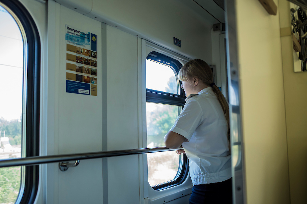 A cabin attendant looks out the window of a passenger train from Kyiv to Donetsk just before arrival on Sunday, July 27, 2014 in Donetsk, Ukraine.