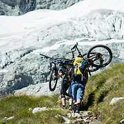 Mountain bikers carry bicycles up steep Höhbalmen Höhenweg trail, below Ober Gabelhorn (4063 m/13,330 ft) and Arben Glacier in the Pennine/Valais Alps, Switzerland, Europe. From Zermatt, hike the scenic Höhbalmen Höhenweg loop via Bergrestaurant Edelweiss, Trift Hut and Zmutt. With delightful views, this strenuous loop accumulates 1200 meters vertically, up and down over 21.6 km (13.4 miles).