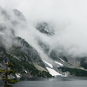 Fog at Snow Lake (elevation 4400 feet) in Alpine Lakes Wilderness Area, Mt. Baker-Snoqualmie National Forest Trail #1013, in the Cascade Range of Washington, USA. Take Interstate 90 Exit #52 westbound or Exit #53 eastbound and follow signs to Alpental Road ski area parking lot and trailhead. To avoid crowds at this popular trail, start early and avoid sunny weekends. The trail down from the saddle viewpoint to Snow Lake is often snow covered through July 4.