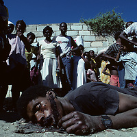 Haiti, Port-au-Prince, Crowd gathers around corpse of man killed in political violence during 1987 elections