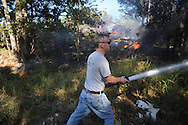 Lafayette County fireman Larry Brown fights a fire on County Road 121 near Abbeville, Miss. on Wednesday, September 29, 2010.