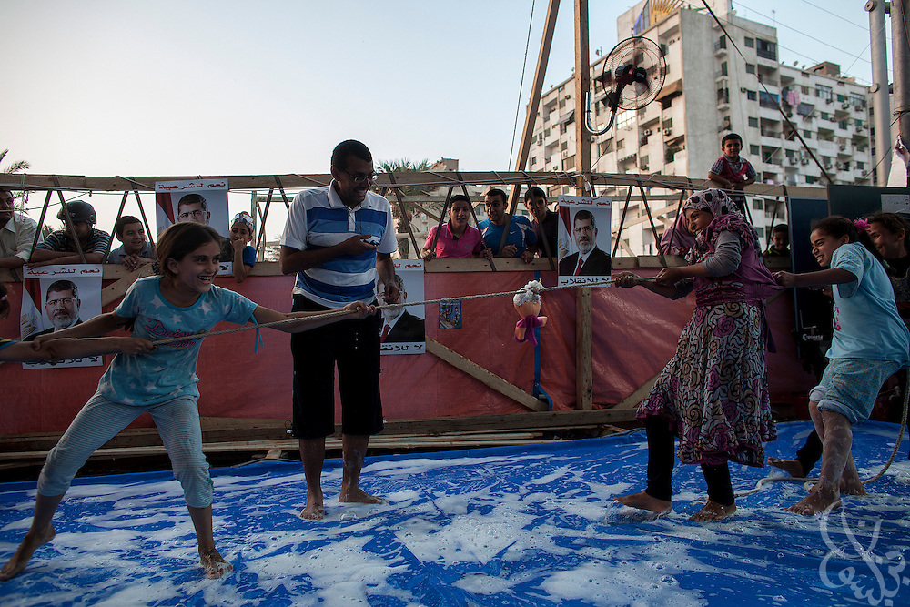 Children of the supporters of deposed Egyptian President Mohamed Morsi play tug-of-war at a kids' play area August 12, 2013 at the entrance of an ongoing sit-in protest camp at the Rabaah al-Adawiya square in the eastern Nasr City district of Cairo, Egypt. The crowd at the camp, made up of men, women and children from various anti-coup coalition groups remains defiant in spite of threats by security officials to forcibly break up the camps soon. Opposing groups and human rights organizations have criticized what they see as exploitation of the children for political gain and use of women and children as human shields in order to deter action by security forces against the sit-in.enjoy time at a playground August 12, 2013 at the entrance of an ongoing sit-in protest camp at the Rabaah al-Adawiya square in the eastern Nasr City district of Cairo, Egypt. The crowd at the camp, made up of men, women and children from various anti-coup coalition groups remains defiant in spite of threats by security officials to forcibly break up the camps soon. Opposing groups and human rights organizations have criticized what they see as exploitation of the children for political gain and use of women and children as human shields in order to deter action by security forces against the sit-in.