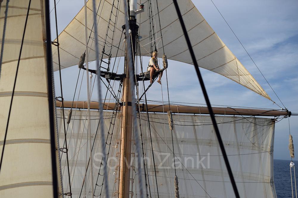 Corwith Cramer is a 134-foot steel brigantine built as a research vessel for operation under sail. Sargasso Sea, Bermuda | Sailing Intern - Gabrielle Page repariert die Saling auf dem Forschungssegler Corwith Cramer. Der Forschungssegler Corwith Cramer durchquert im April 2014 die Sargasso See von Puerto Rico kommend bis zu den Bermuda Inseln.