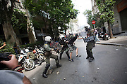 A protester is caught amongst the clashes with poilce in the side streets of Athens, Greece.  The MPs in parliament prepare to debate new austerity measures required for the EU and IMF bail-out package.  Athens turned into a war zone with many arrests and tear gas thrown by the police.  Image © Angelos Giotopoulos/Falcon Photo Agency