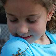 A young girl enjoys watching a lizard crawling on her shoulder.