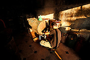 Yazans (c) gaz station located in the basement of his private house is completely black grimed since a fuel explosion killed his brother. Since regular fuel distribution collapsed in Syria motorized mobility relys on very basic equipped improvised gaz stations and often dangerous simple handling with low quality fuel from rebel or IS held areas of Syria.<br />