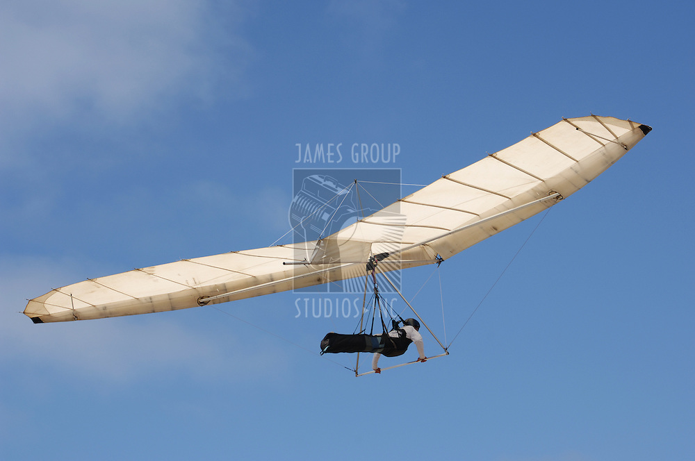 Fixed wing hang glider and pilot against a blue sky