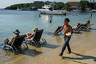 Tourists line the beach at Roatan, one of the Bay Islands off the coast of Honduras. Many retirees from the US settle there and most citizens speak English.