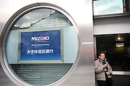 A man looks at his cell phone next to a branch of Mizuho in Tokyo, February 2, 2009. Mizuho Financial Group, Japan's second-largest bank, swung to a $565 million loss for the first nine months of the business year, hurt by losses on its stock portfolio and a weak economy, and it cut its full-year forecast again.