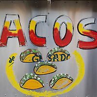 A hand painted sign on a taco cart.