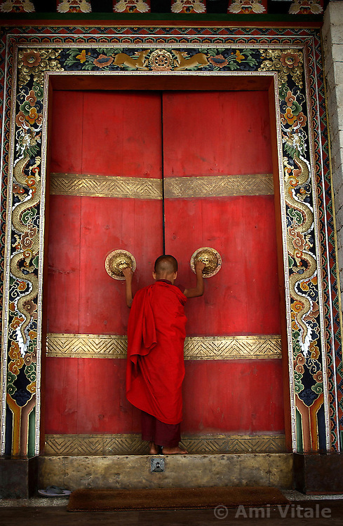 "A Buddhist monk enters the formidable doors of Trongsa Dzong, the Ancestral home of Bhutan's monarchy. The Himalayan kingdom of Bhutan has sat in isolation for thousands of years and only recently has been thrust into the glare of modern times after centuries of solitude. Bhutan is a tiny, remote, and impoverished country wedged precariously between two powerful neighbors, India and China. Violent storms coming off the Himalaya gave the country its name, meaning ""Land of the Thunder Dragon."" This conservative Buddhist kingdom high in the Himalaya had no paved roads until the 1960s, was off-limits to foreigners until 1974, and launched television only in 1999 ."