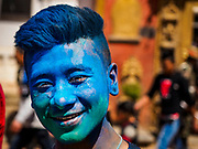 12 MARCH 2017 - BHAKTAPUR, NEPAL: A man with blue powder on his cheek at a Holi celebration in Bhaktapur. Holi, a Hindu religious festival, has become popular with non-Hindus in many parts of South Asia, as well as people of other communities outside Asia. The festival signifies the victory of good over evil, the arrival of spring, end of winter, and for many a festive day to meet others. Holi celebrations in Nepal are not as wild as they are in India.     PHOTO BY JACK KURTZ